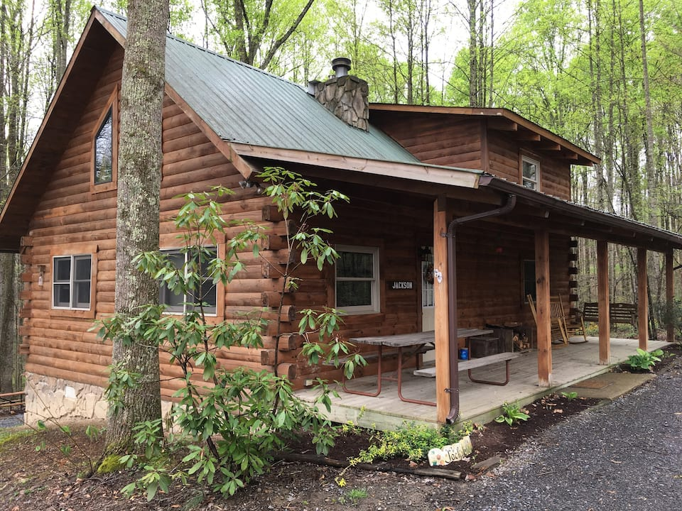 Beautiful log cabin in West Virginia with generous front porch surrounded by green forest.