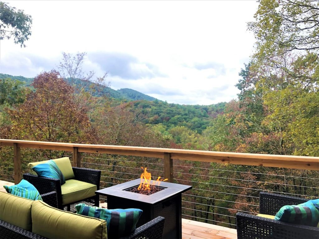 This mountain top cabin in West Virginia displays the spectacular view of the valley from balcony with lovely patio furniture placed around the fire in the fire pit.