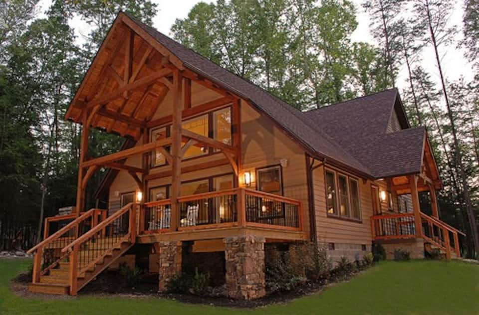 Large brown luxury cabin with lights illuminating it with spacious front porch makes this one of the best Summerville Lake Cabins in West Virginia.