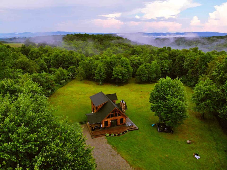 Overhead photo of log cabin surrounded by forested treed and fog covering mountains in background.