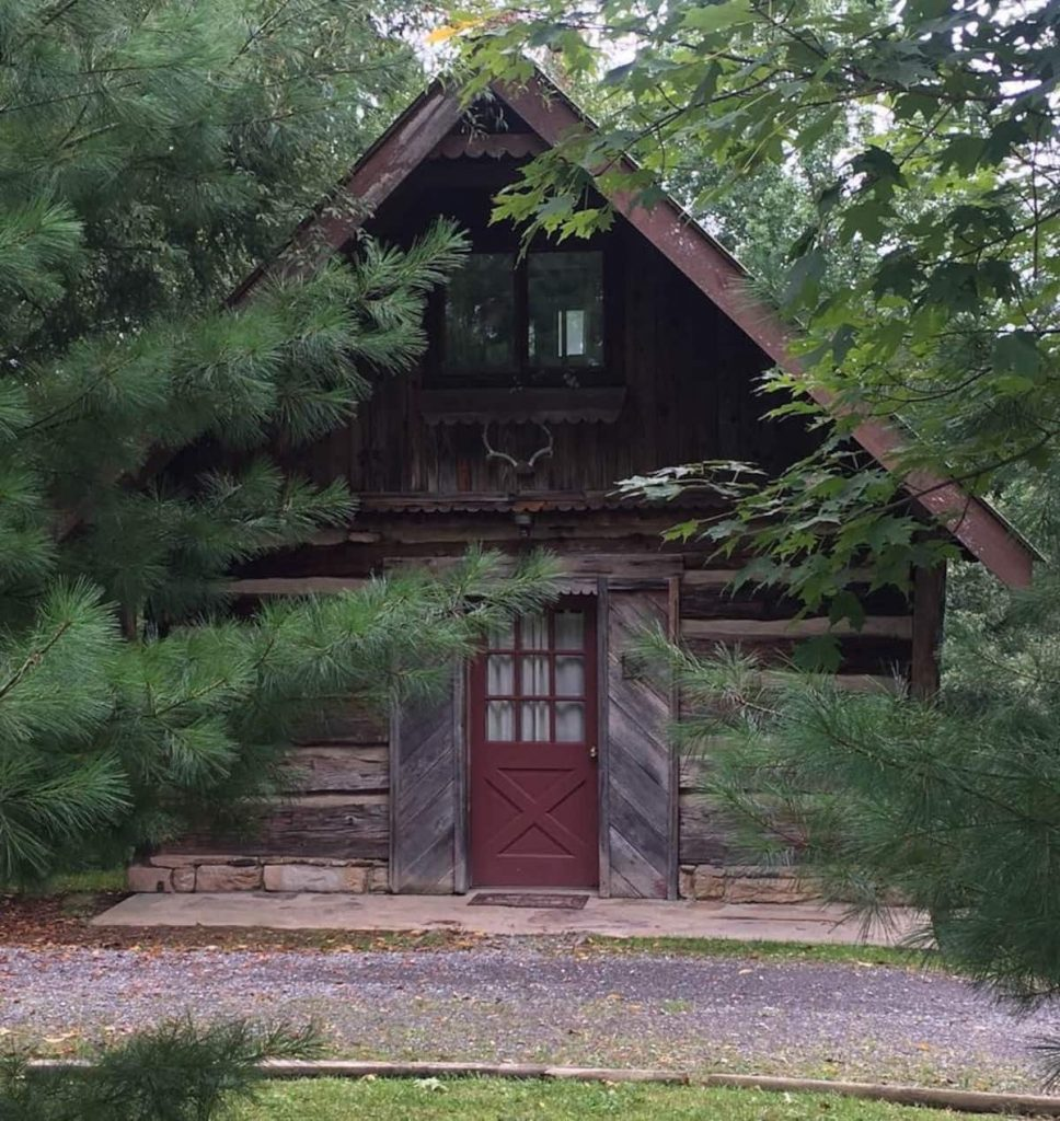 Romantic log cabin with burgundy front door surrounded by fir trees.