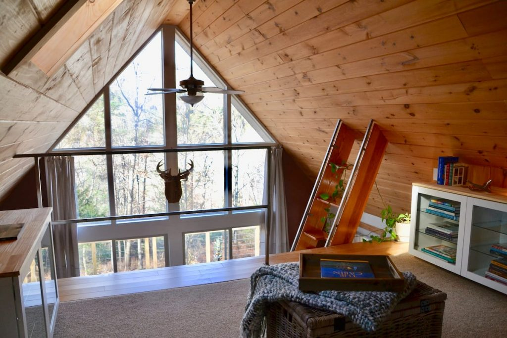 Spectacular view of outdoors from the floor to ceiling glass windows in this cozy West Virginia cabin.