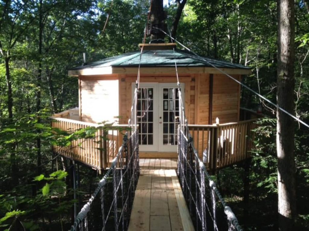 Octagonal treehouse cabin with suspension bridge leading to double-French doors is one of the coolest cabins in West Virginia.