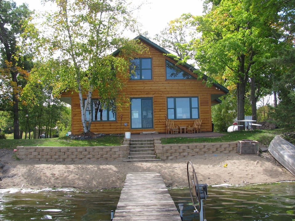 Stunning log cabin with large windows and green trees surrounding it. Private sandy beach and lake waters in foreground.