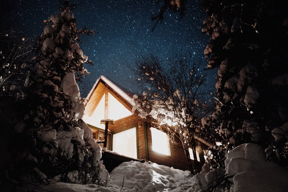 Dreamy cabin in Minnesota, at night, bright lights shining from its large windows with starry sky in background.