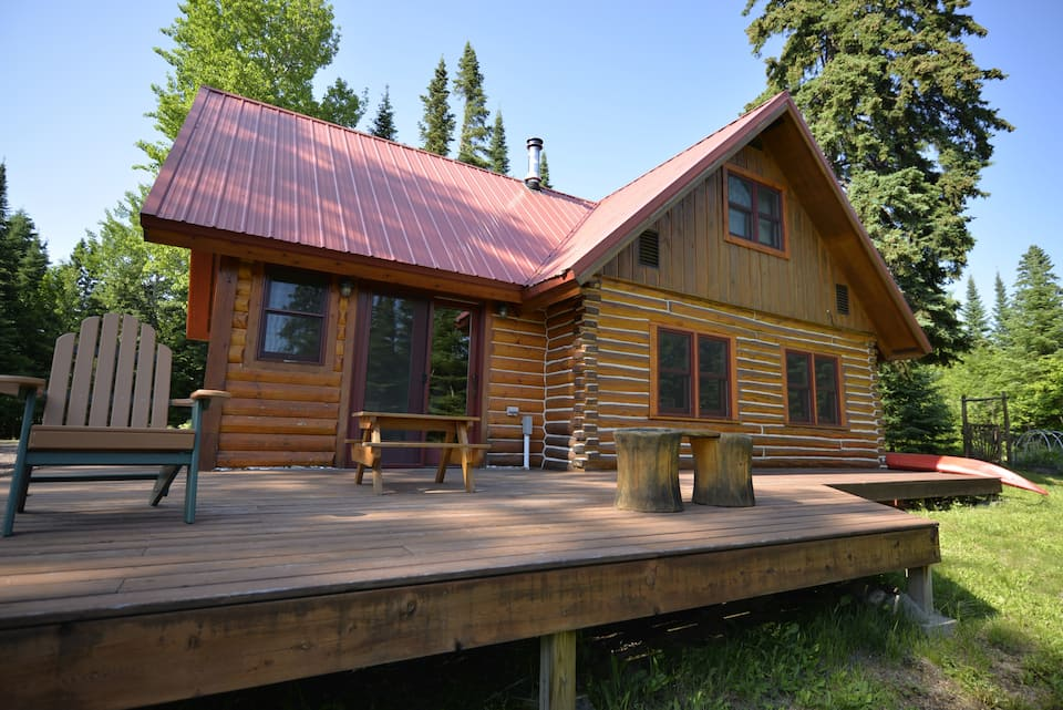 Spectacular log cabin with red metal roof and large deck with Adirondack chairs.