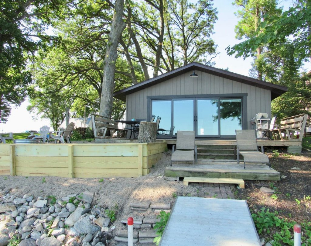 Lovely cabin with large sliding doors, with decking and patio furniture with sandy shoreline.
