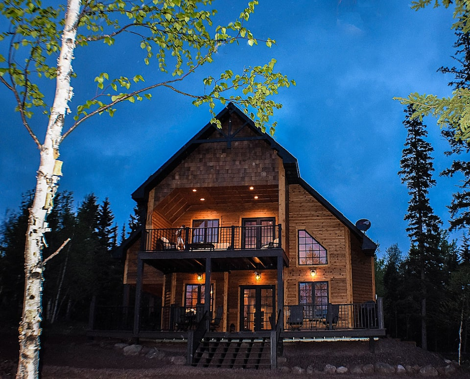 Beautiful cabin with large windows with large front porch and balcony, with romantic lights against blue night sky.