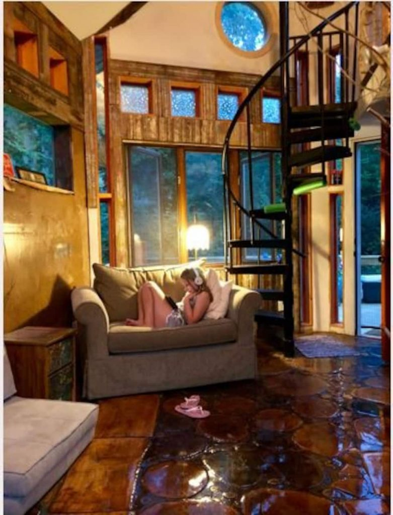Photo of young girl relaxing on sofa in Minnesota cabin with spiral staircase and large windows throughout the room.