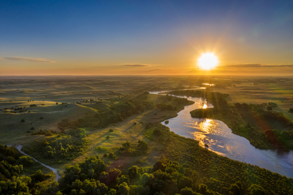 Photo of river meandering though Nebraska sandhills with sun setting in background.