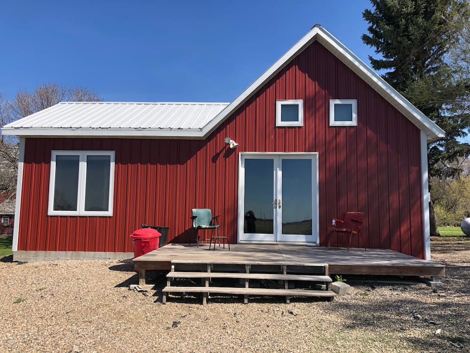 One of the coolest cabins in North Dakota is this red-sided one with double French doors leading out to back wooden patio and two lounge chairs.