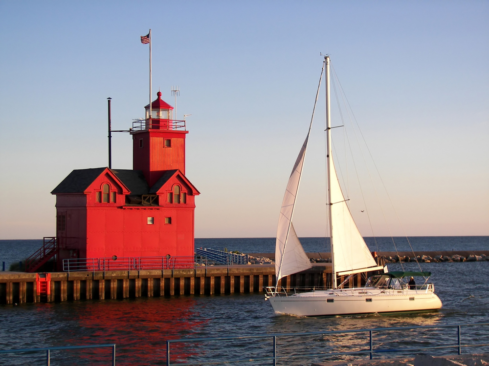 large red lighthouse with a sail boat in front of it