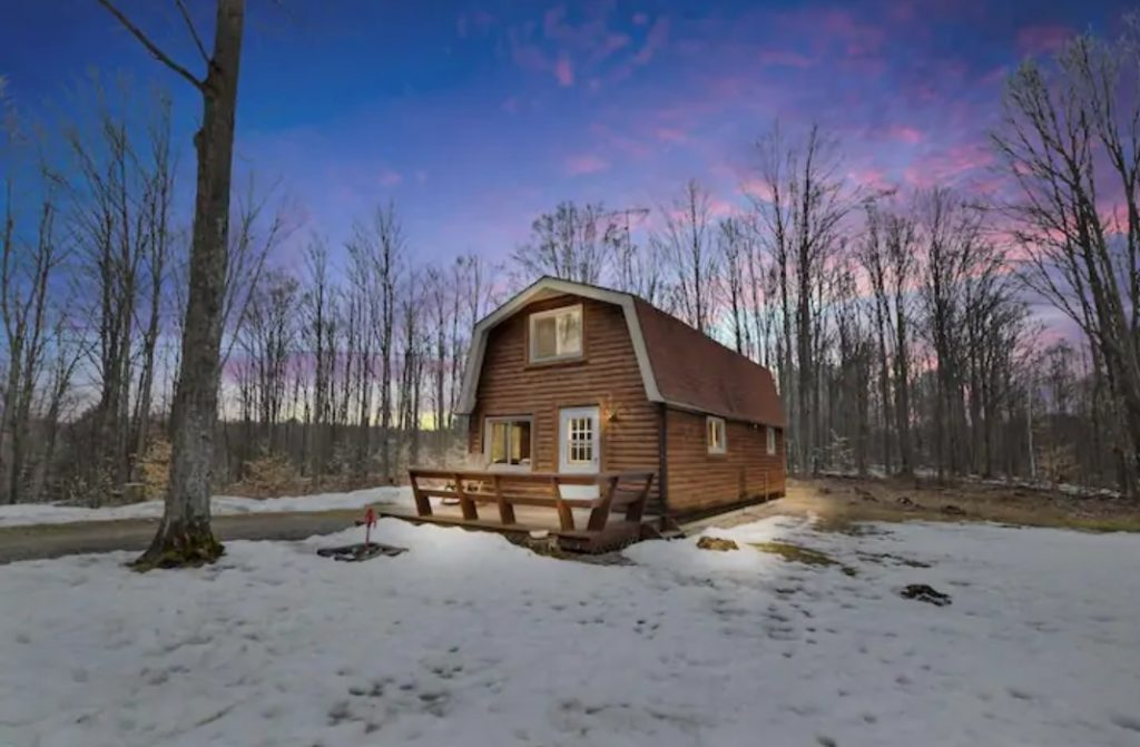 A barn style cabin in the middle of the woods surrounded by trees with snow on the ground during sunset cozy cabins in Michigan