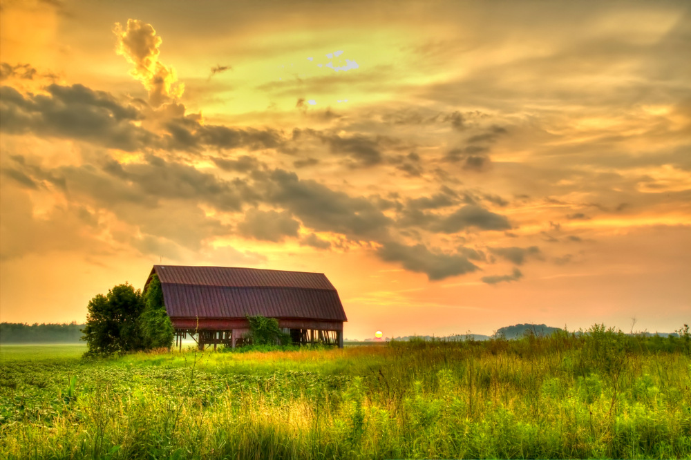 Iconic Iowa barn at sunset with sky brilliant yellow.