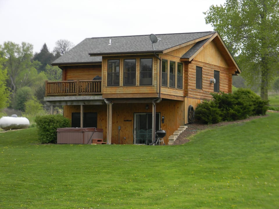 Large cabin with hot tub, deck, large windows  surrounded by nice green yard.