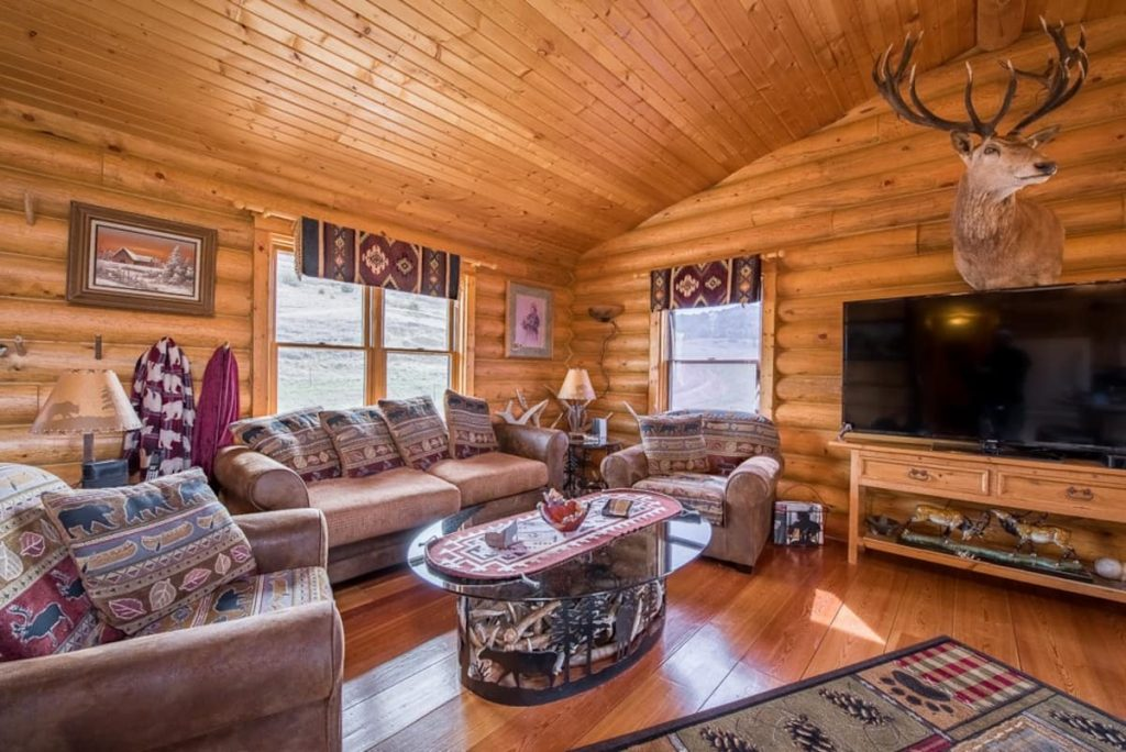 Log cabin main living space with comfy living room furniture and large screen tv, in one of the coolest cabins in North Dakota.