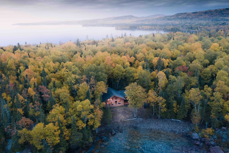 Overhead shot of Log cabin in Minnesota surrounded by forested trees with Lake Superior in background, and cove of water in front of cabin.