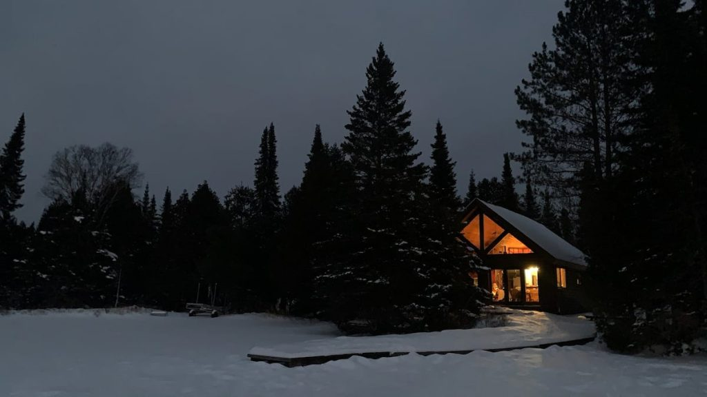 Fairytale-looking Minnesota cabin illuminated from within on a dark snowy night.