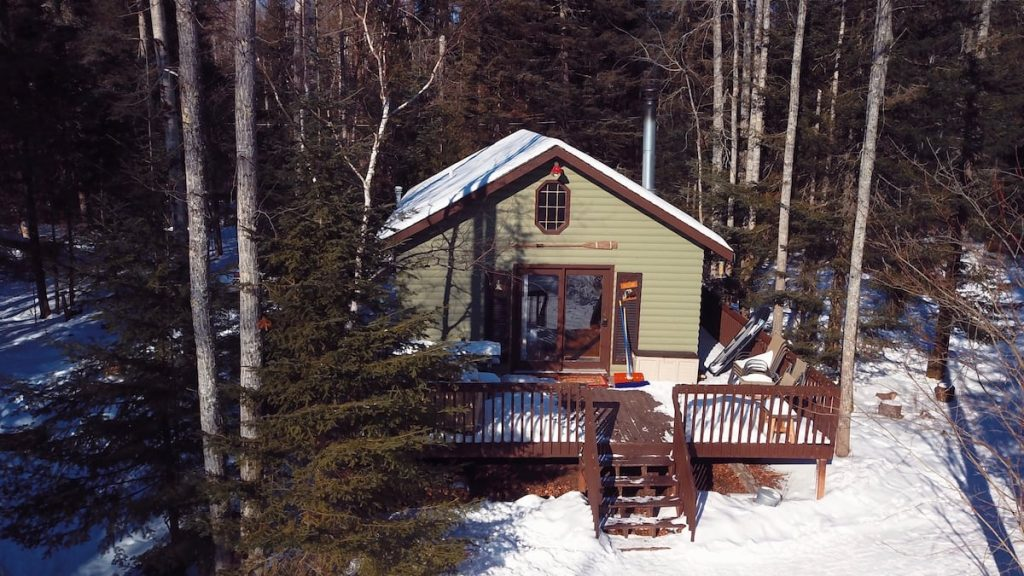 Cozy beige cabin with brown trim, and sliding glass doors leading out to back patio in the winter time with snow on the ground.