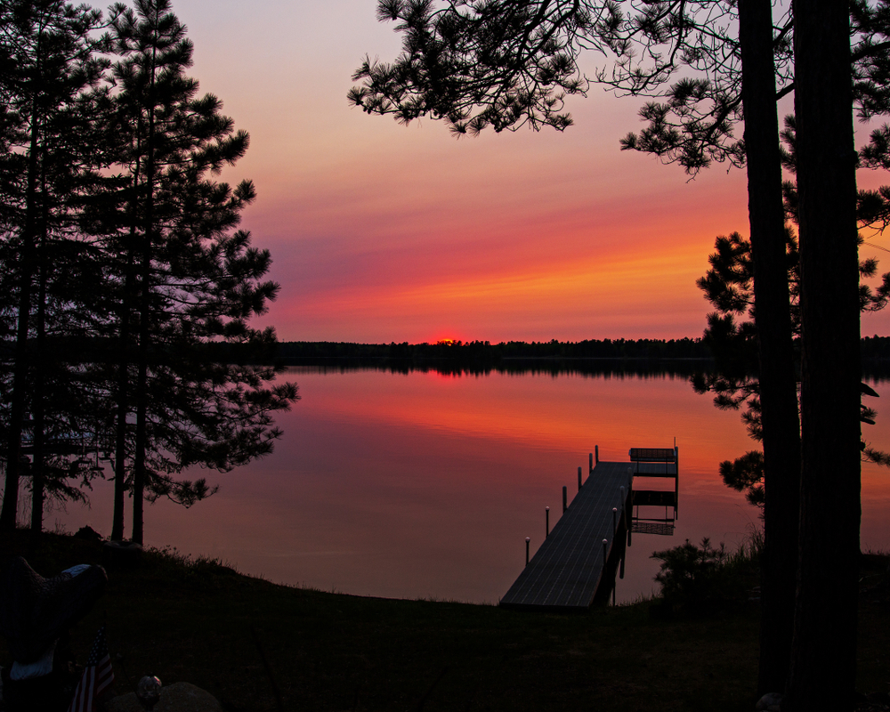 Orange sunset over a lake in Northern Minnesota. A dock in in the foreground.