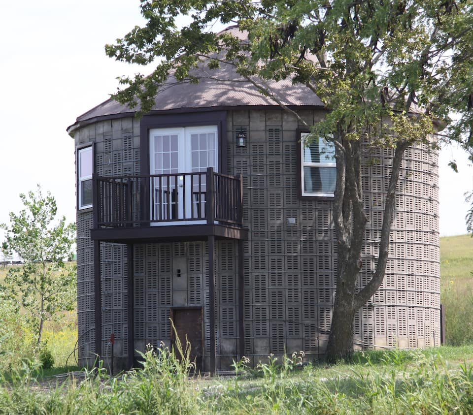Brown circular corn crib with balcony, now a cabin in Nebraska.
