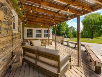 One of the coziest cabins in Iowa, this one has an Americana vibe with its front porch. It has wooden floor, walls and comfy furniture.