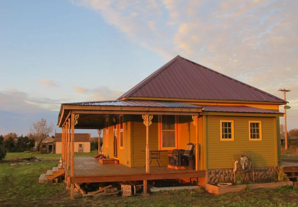 A charming 1915-era Folk Victorian cottage painted an olive green with a large porch that overlooks the Cannonball River at sunset