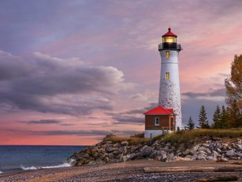 white lighthouse in Michigan with sunset sky in background.