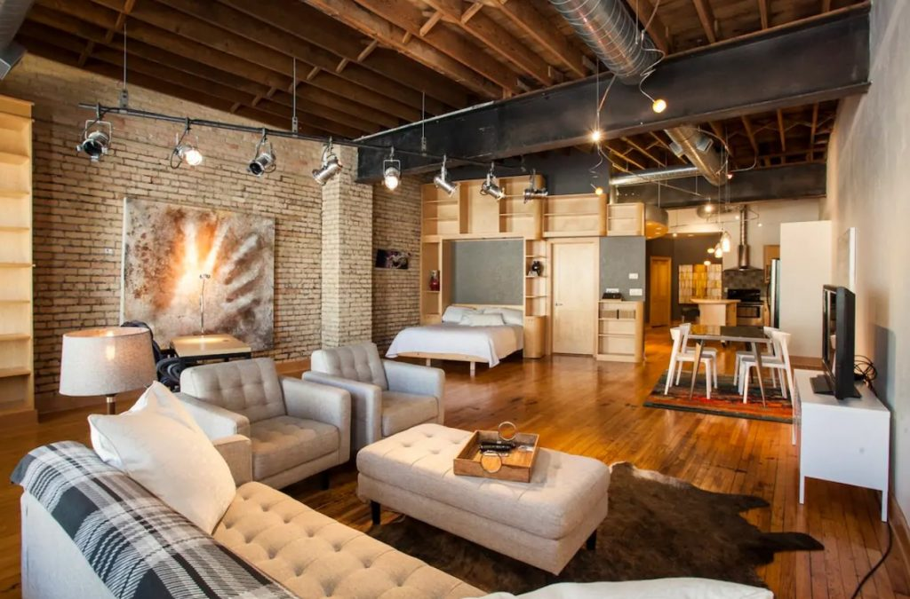 A large studio loft space with a sitting area, a queen-sized bed, a dining table, and a full kitchen with brick walls, wood beams on the ceiling, and art from local artists.