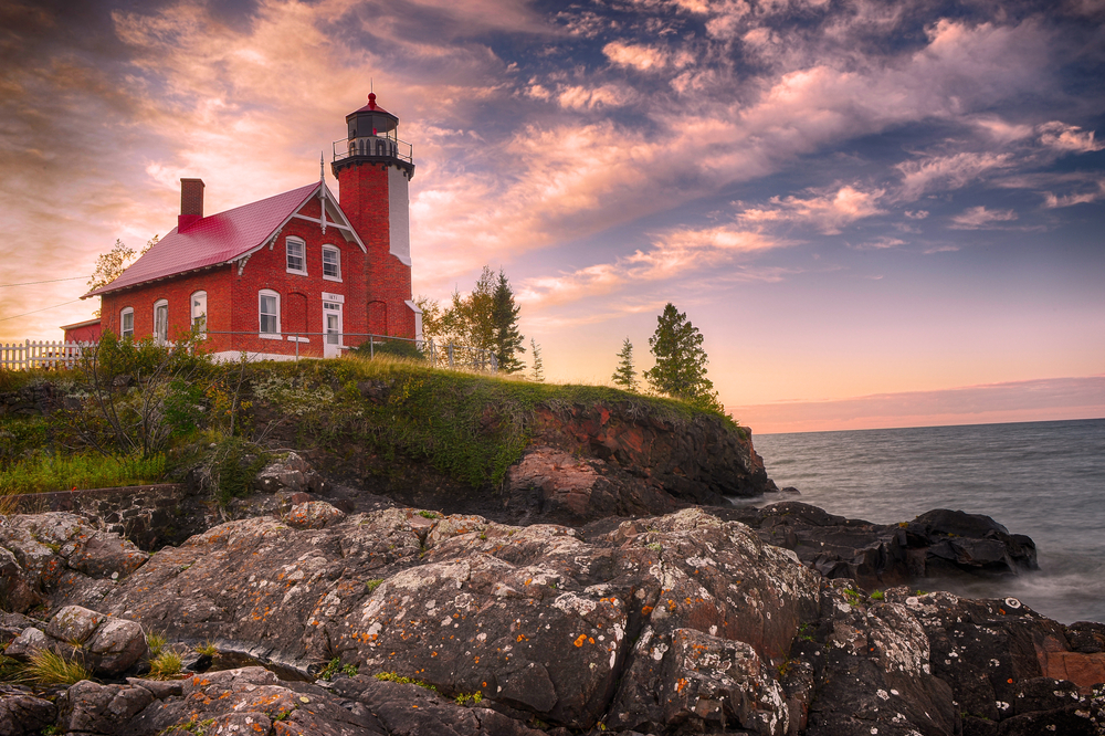 Sunset over a large red lighthouse on the rocky edges of Lake superior