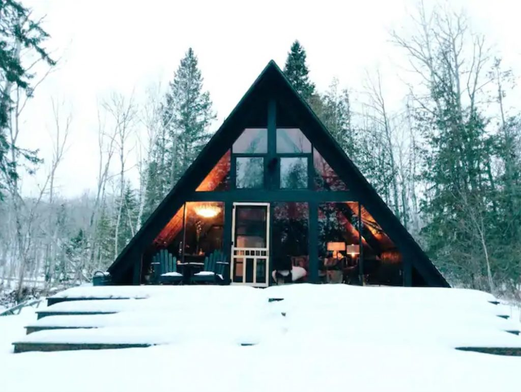 An A-frame cabin with a large front porch covered in snow surrounded by trees with floor to ceiling windows