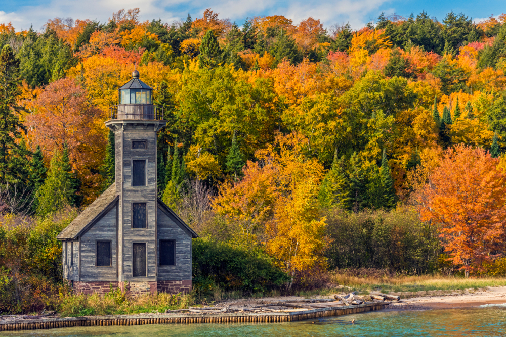 An abandoned wooden lighthouse on the shores of Lake Superior with a large forest behind it with the leaves changing in fall coolest lighthouses in Michigan