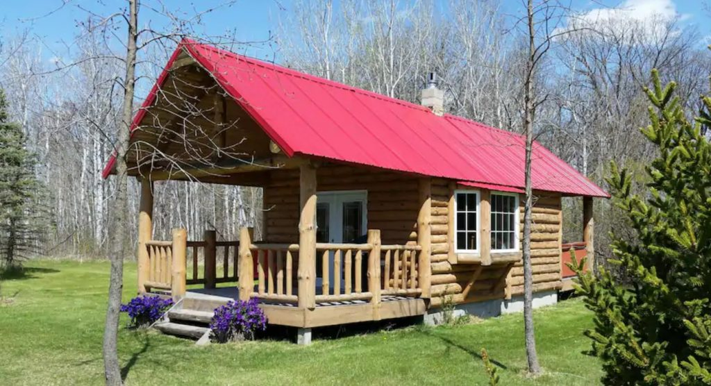 The exterior of a one room classic log cabin with a red roof and a large covered front porch