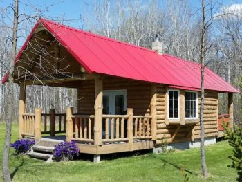 Log cabin with red rood and large front porch.