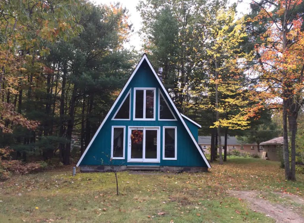 A teal A-frame cabin with white trim on a grassy plot of land with trees behind it