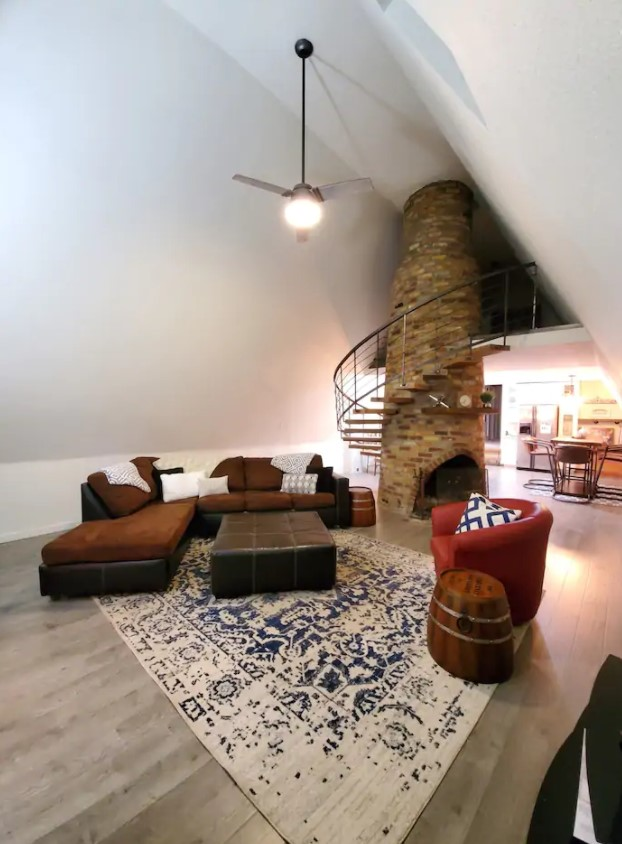 A living room with a large brick circular fireplace in the middle of it with a spiral staircase around it