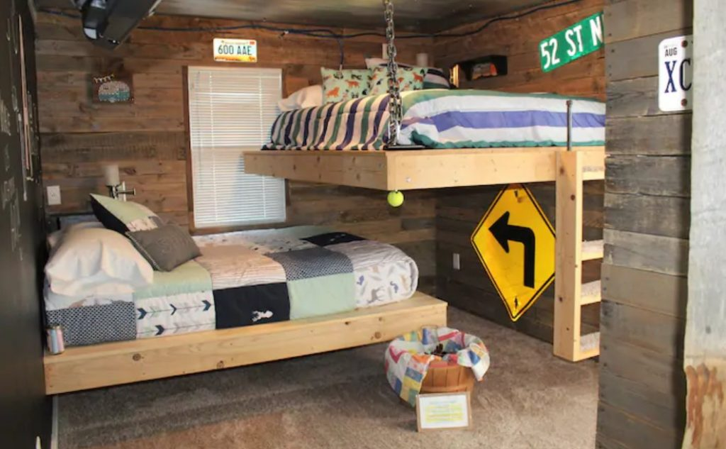 A wood paneled room decorated with traffic signs with two uniquely designed full-sized bunk beds