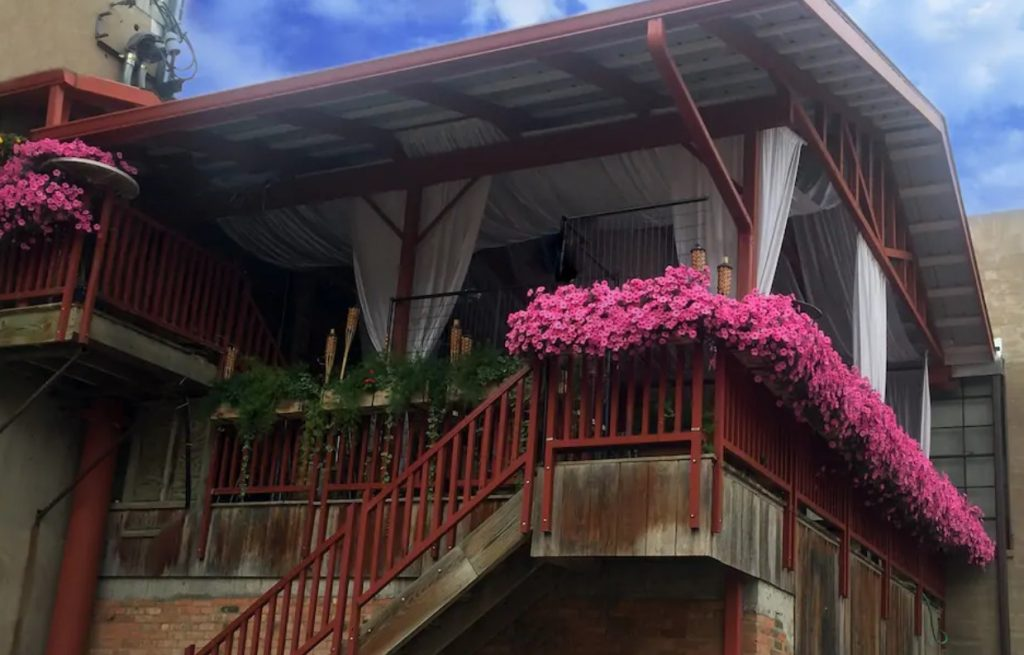 A large deck with a white wooden roof, white curtains, tiki torches, and pink flowers on the railing airbnbs in North Dakota