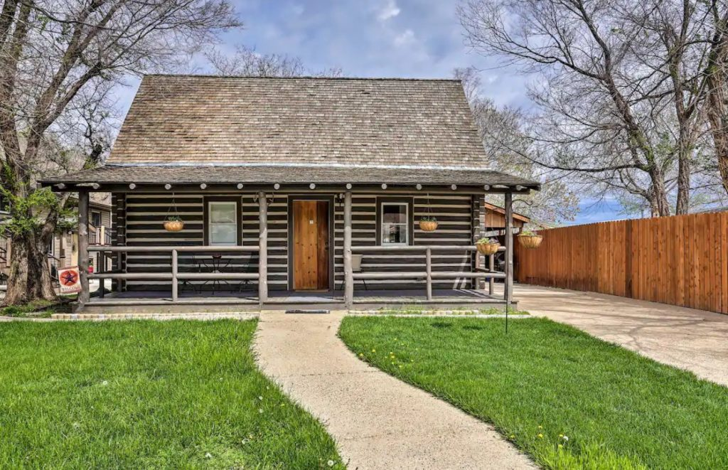 The exterior of a classic log cabin with a long fence next to it and a large green front yard