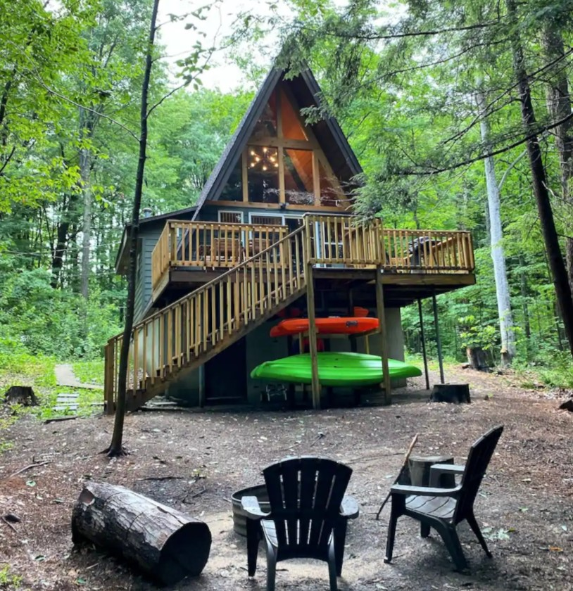 An A-frame cabin with a large deck, kayaks, a fire pit, and floor to ceiling windows surrounded by trees