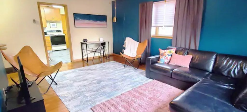 A large living room with a sectional sofa, two butterfly chairs, and teal and pink accents.