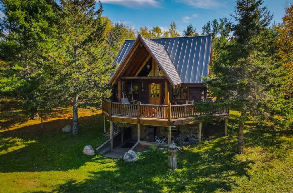 A large two story cabin with a large deck and patio surrounded by trees cozy cabins in Michigan