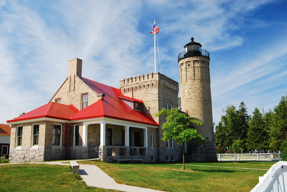 A large stone lighthouse that resembles a castle with a square turret and a red roof lighthouses in michigan