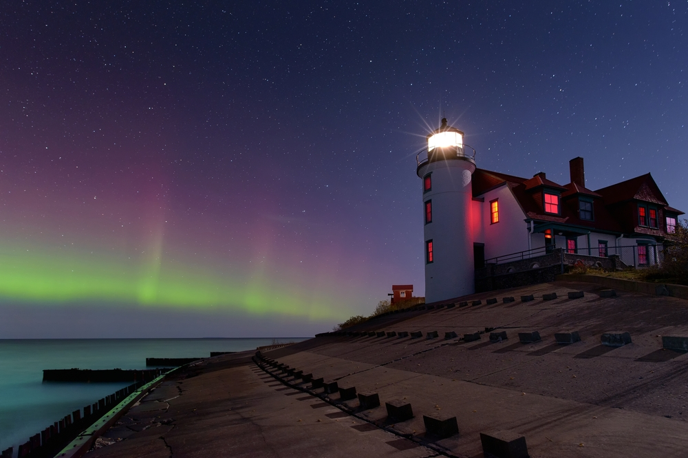 The northern lights in the sky behind Point Betsie lighthouse lit up at night coolest lighthouses in Michigan