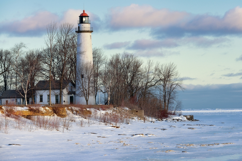 A tall white lighthouse on the edge of Lake Huron in the middle of winter with the lake frozen over and covered in snow