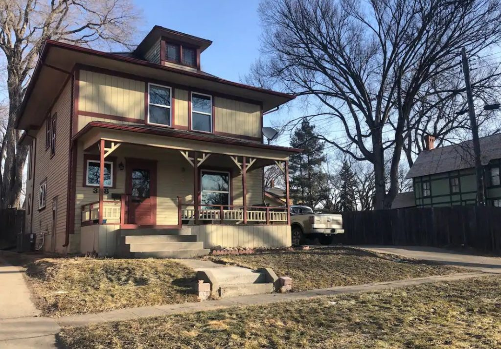 A large beautiful historic home painted tan with brick-red trim best Airbnb in North Dakota