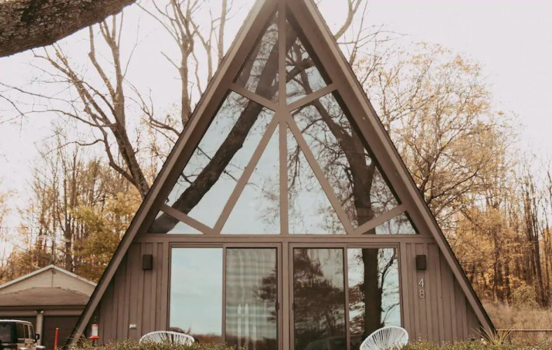 A tan A-frame cabin with floor to ceiling windows in the front and trees behind it