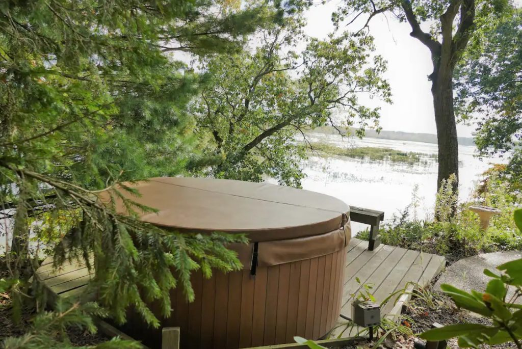 A round hot tub on a secluded deck that overlooks the marsh land in Michigan