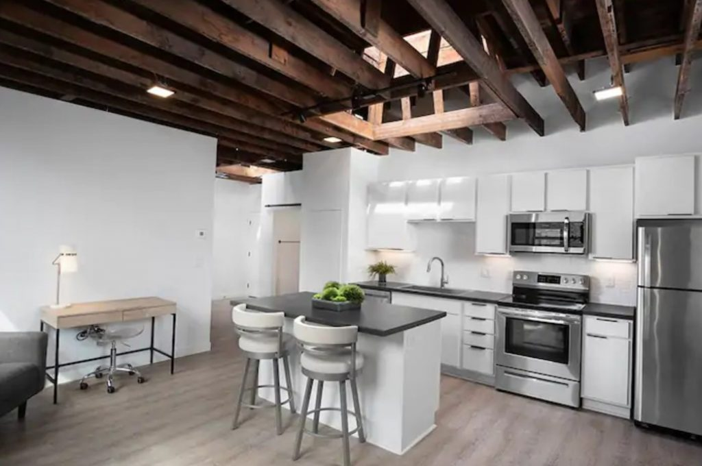 A sleek and modern kitchen with white cabinets, a white island, and black countertops with loft ceilings, wood beams, and a skylight an Airbnb in North Dakota