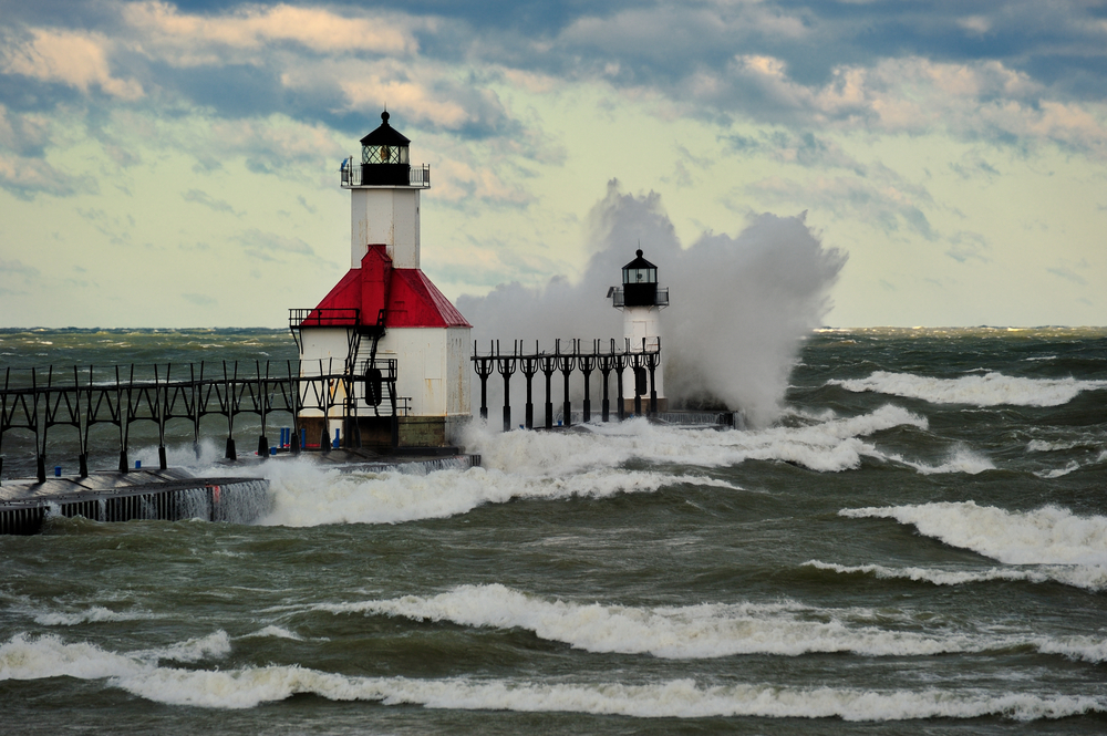 Two light towers connected by a catwalk over Lake Michigan with a wave crashing against it